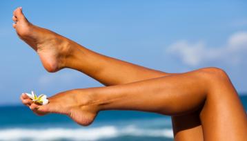 pies perfectos de una chica en la playa con una flor apoyada en el empeine