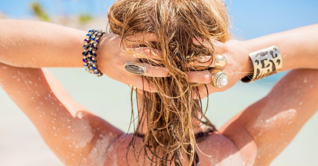 chica de espaldas en la playa se sujeta el pelo mojado con las manos que aparecen llenas de anillos y pulseras