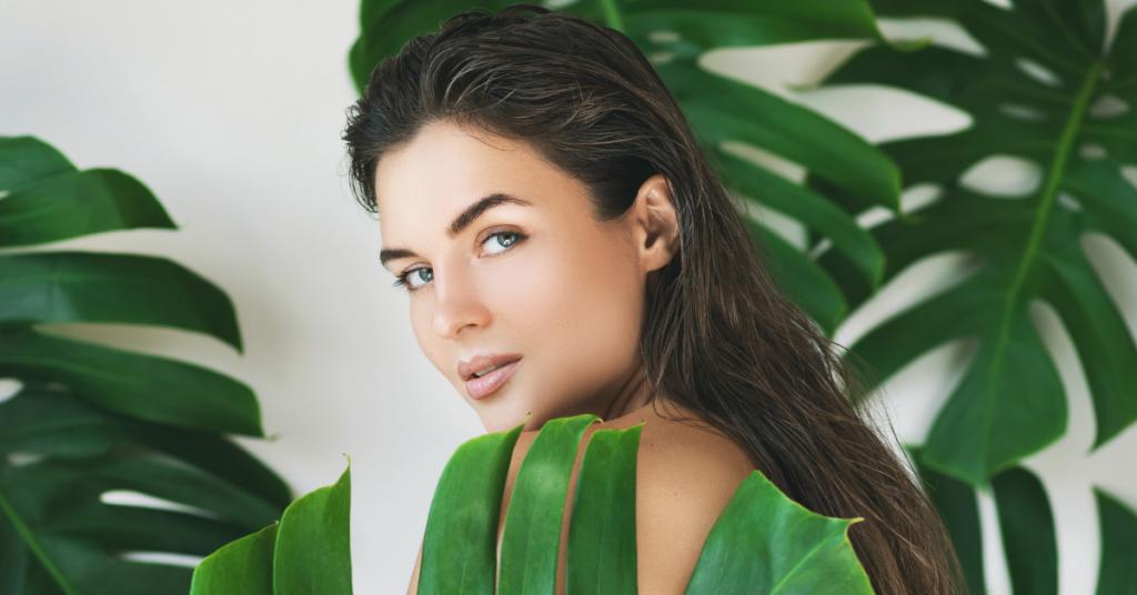 Chica joven mira a cámara entre las hojas de una planta que se llama la costilla de adan