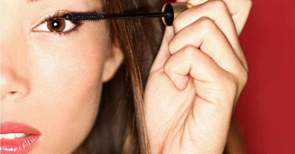 primer plano de la mitad de la cara de una chica joven que se esta echando rimel negro en sus frondosas pestañas