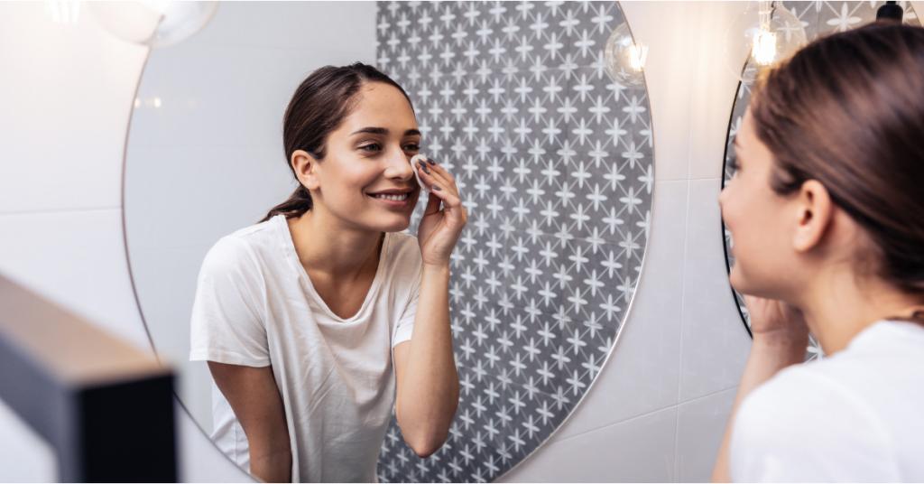 vemos el perfil de una chica y su reflejo completo en un espejo se esta limpiando la cara con un algodon ella es morena de piel y pelo atado en una coleta tiene las uñas pintadas de azul y en el espejo tambiens e refleja una pared con un decorado azul y blanco muy bonito