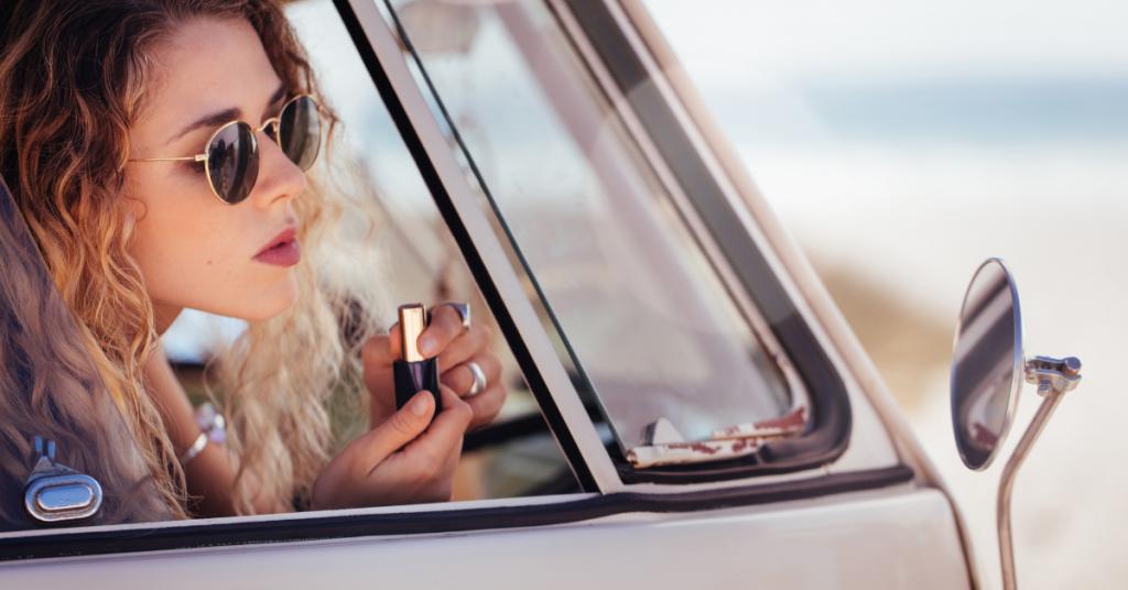 una chica joven con gafas de sol se asoma por la ventanilla de un coche gris para pintarse los labios con el pintalabios marron que tiene en sus manos mirandose en el espejo retrovisor