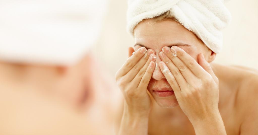 la cara de una chica con una toalla en la cabeza reflejada en unn espejo tiene las manos en los ojos porque se los esta lavando
