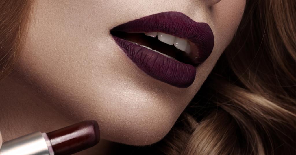 la boca entreabierta de una chica joven que lleva los labios pintados en color burdeos oscuro tambien vemos el pinta labios del mismo color