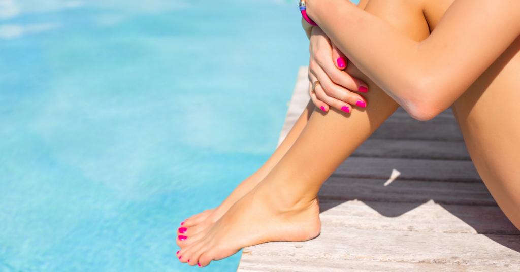 Un cuerpo de perfil sentado en el borde de una piscina con las uñas y los pies pintados de rosa no se ve su cabeza
