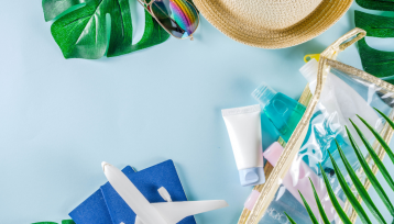 desde un plano superior vemos varios objetos esparcidos en una mesa como un avion de juguete, hojas de plantas, un sombrero, un neceser, cremas, y otros productos que solemos llevar de viaje