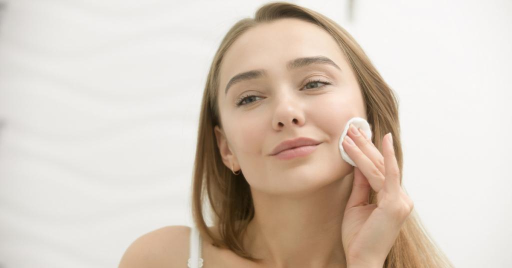 chica joven y rubia mira sonriente mientras se aplica un algodon blanco sobre la cara