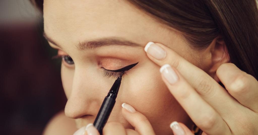 plano detalle de una chica que se maquilla con un eyeliner negro