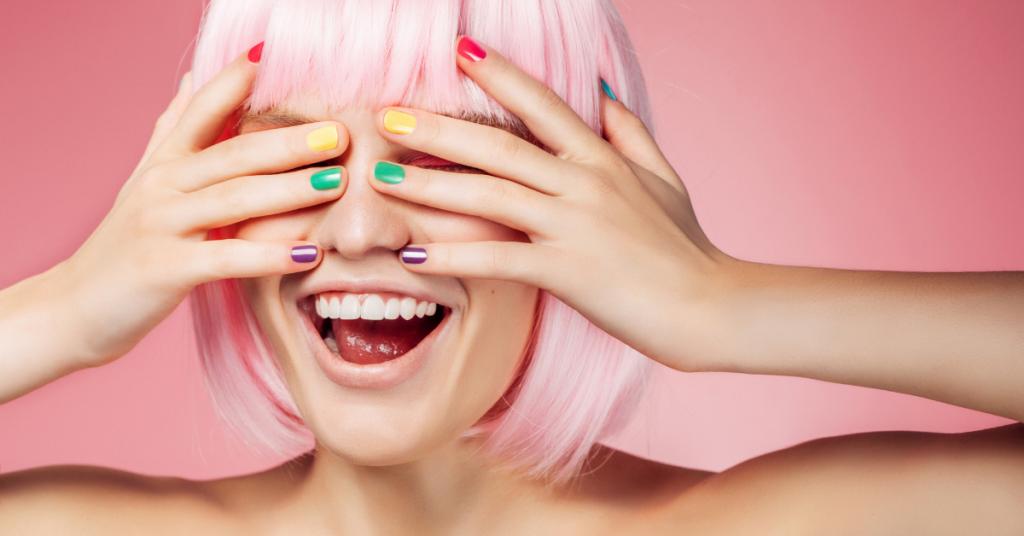 una chica se tapa los ojos y se rie lleva las uñas pintadas cada una de un color rosa amarillo verde y azul el pelo es rosa y corto con flequillo