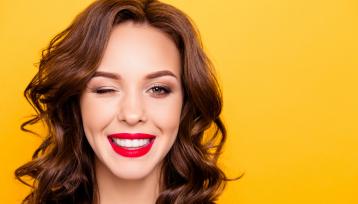 chica joven de pelo castaño sonrie con los labios pintados de rojo sobre un fondo naranja