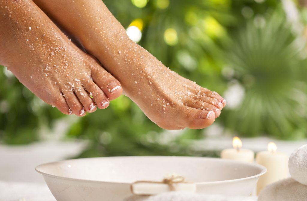 pies de mujer tienen un exfoliante aplicado se ve un bonito cubo con agua y plantas verdes al fondo