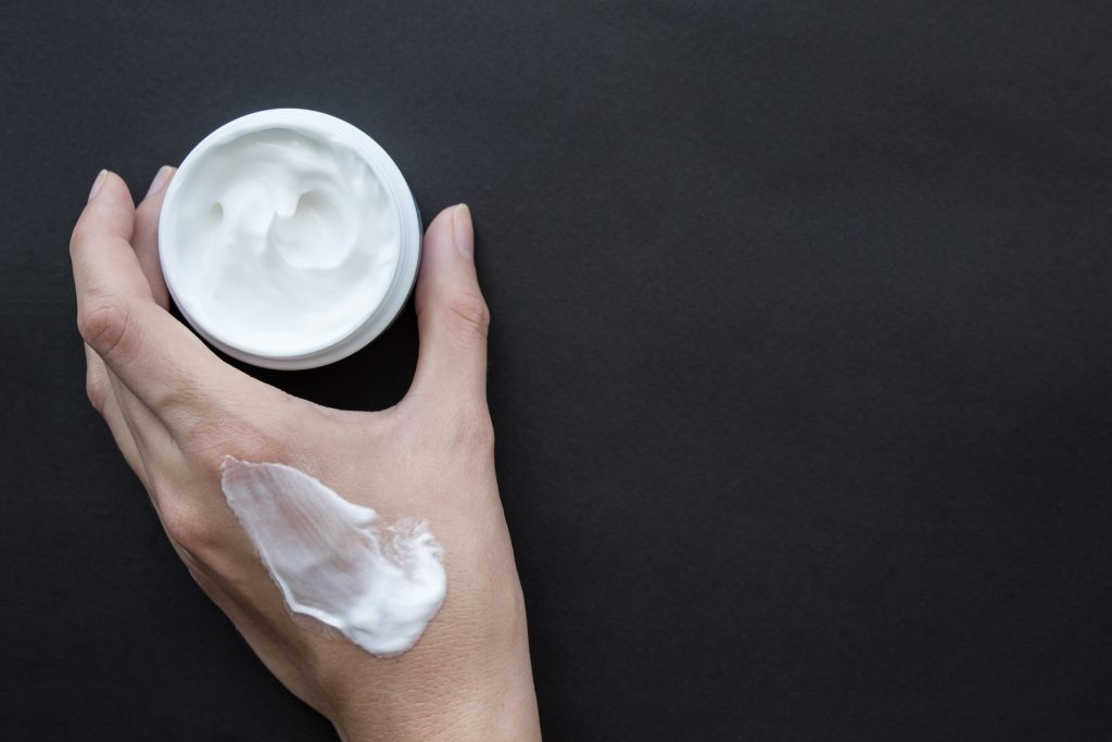 Cream for face or body in female hand. Smear cream on hand