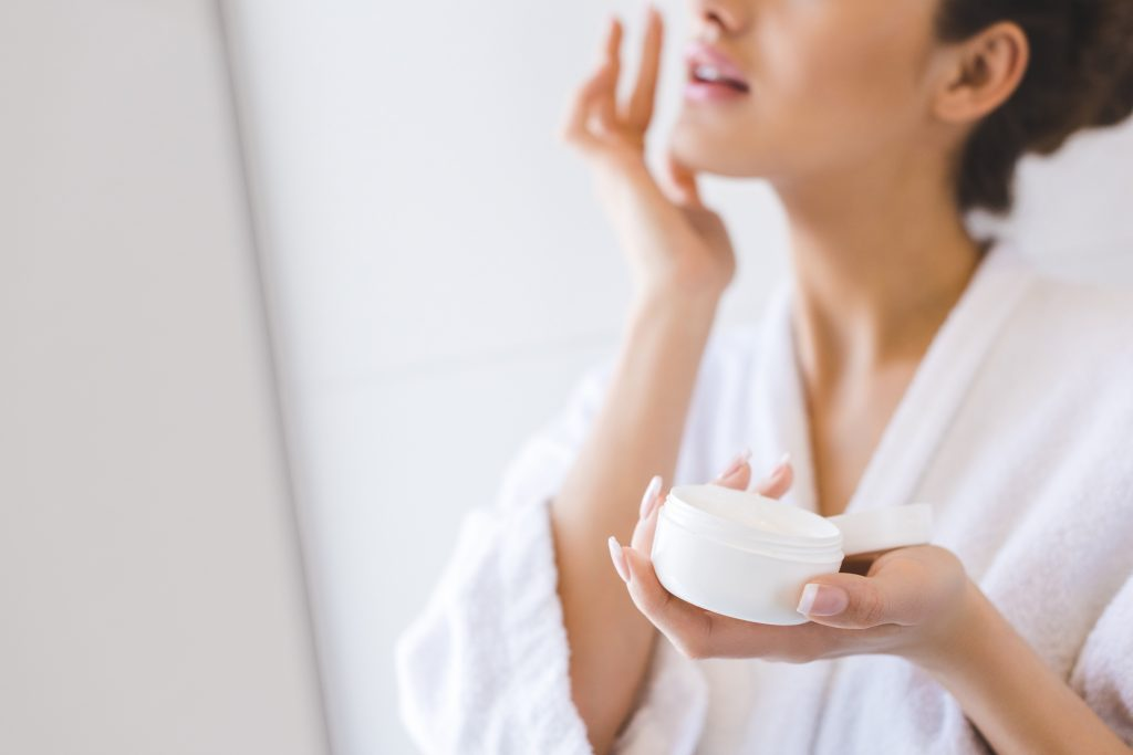 cropped shot of beautiful woman in bathrobe applying face cream
