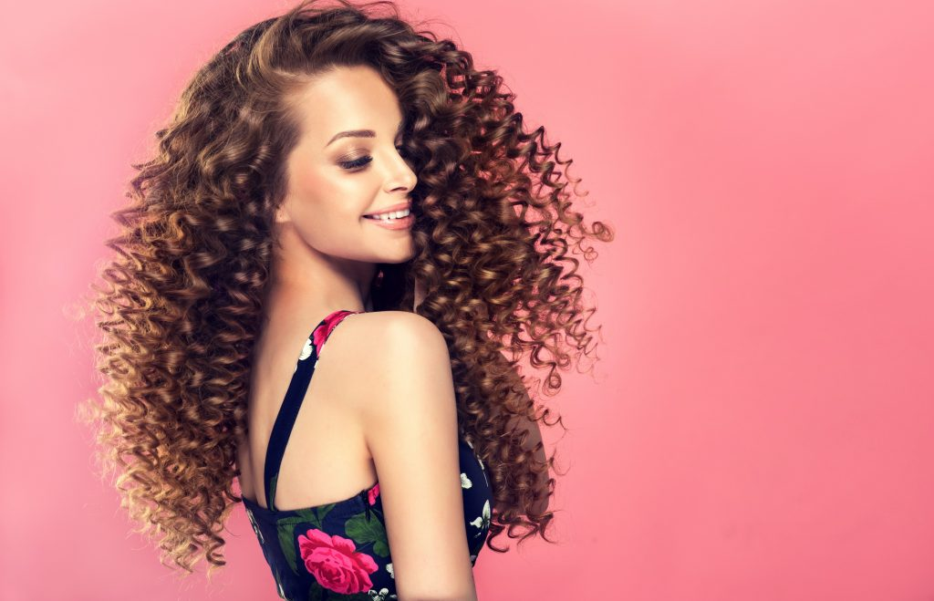 Young, wide smiling brown haired woman with voluminous hairstyle in profile. Beautiful model with long, dense, curly hairstyle and vivid makeup. Dense, spring-like,elastic curls in a hairstyle of young, pretty model. Frizzy hair.
