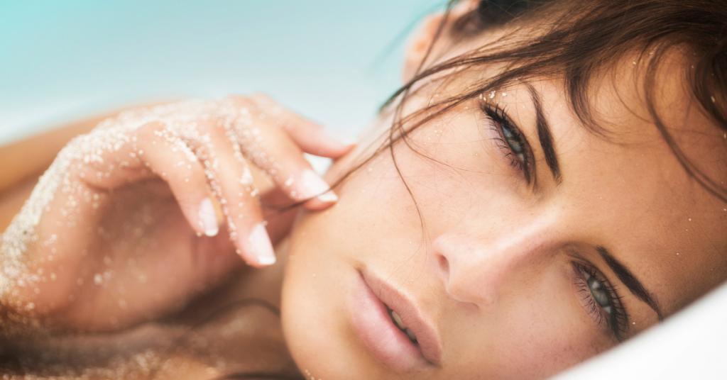 el rostro de una chica girada mirando a camara seria tiene la mano apoyada en la cara y esta llena de arena blanca como de playa paradisiaca