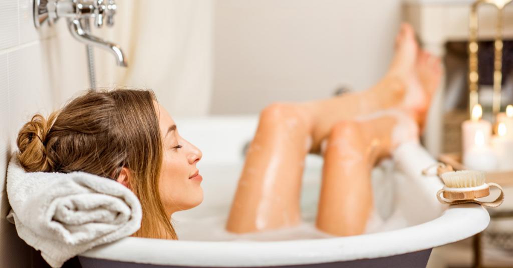 chica se da un baño relax en una gran bañera con las piernas por fuera una toalla bajo su cabeza