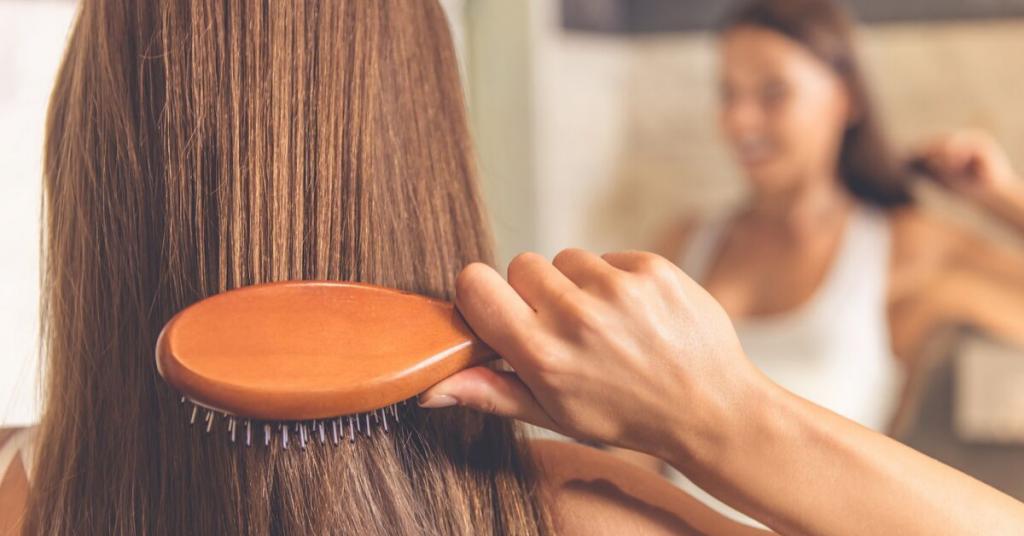 De espaldas la mano de una chica joven cepilla su pelo mientras vemos su reflejo al fondo de la imagen