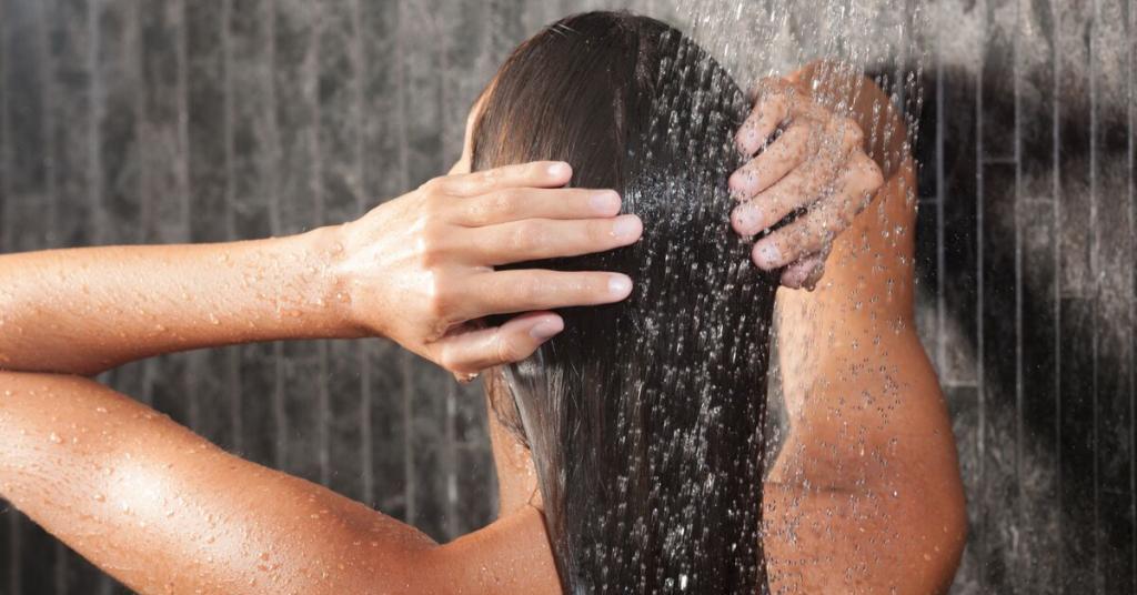 chica joven de espaldas lava su melena bajo la ducha
