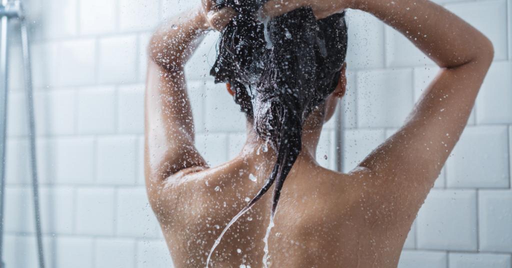 una chica de espaldas se lava el pelo bajo la ducha