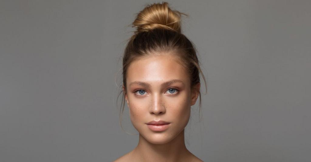 chica joven mira a camara con el pelo recogido en un moño alto y la tez ligeramente maquillada