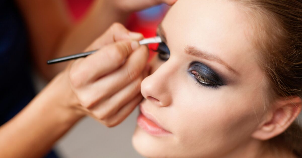 manos de una maquilladora pintan de negro las sombras de los ojos de una modelo joven