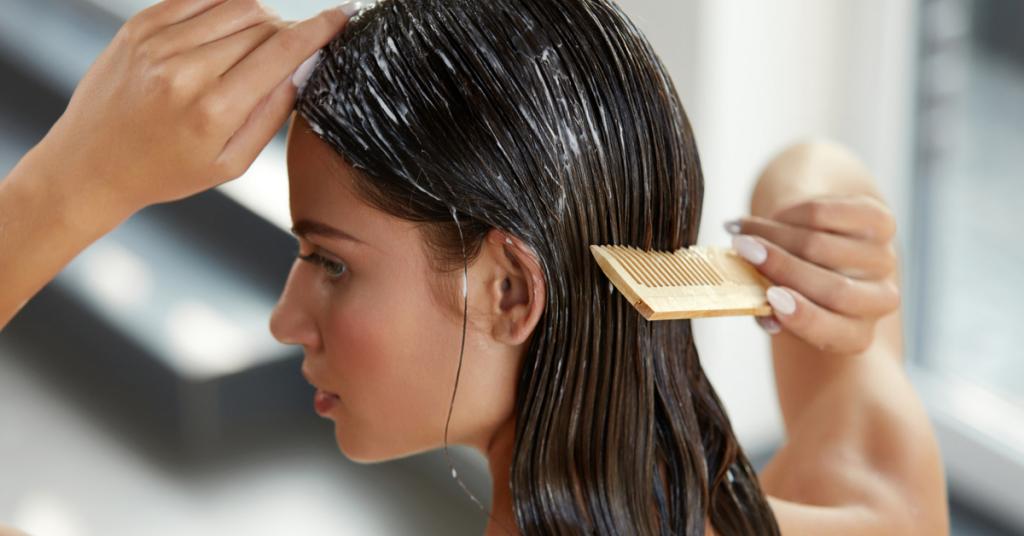 chica joven de espaldas se peina el pelo con una mascarilla echada
