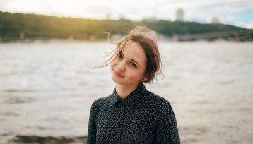 chica joven mira a camara con la cabeza torcida, el pelo recogido y un rio con la ciudad de fondo