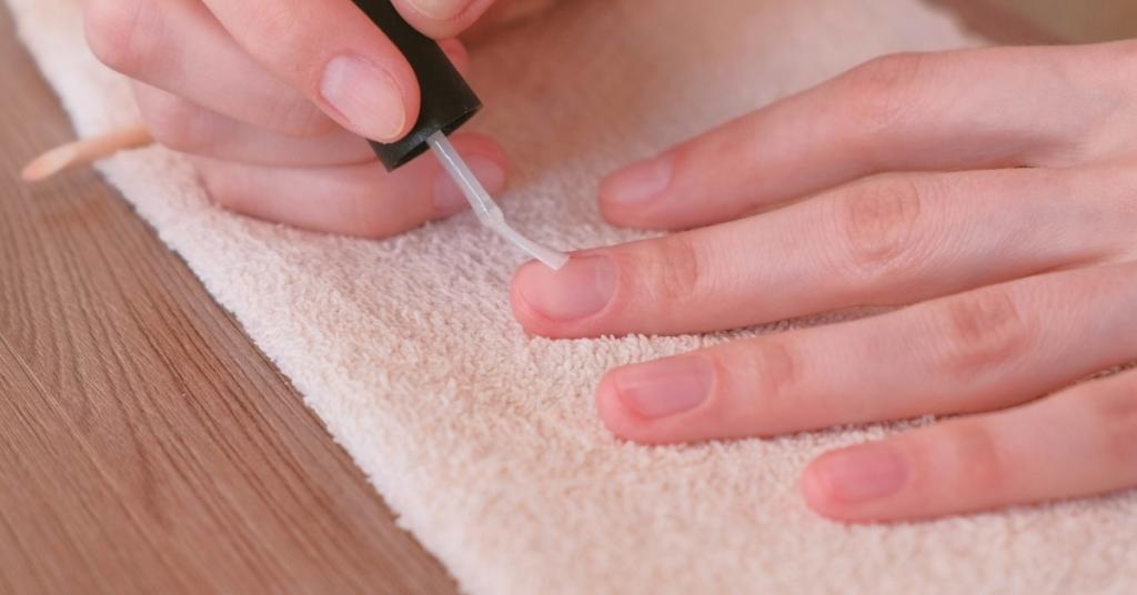 unas manos de mujer pintan con esmalte transparente sobre las uñas de su otra mano