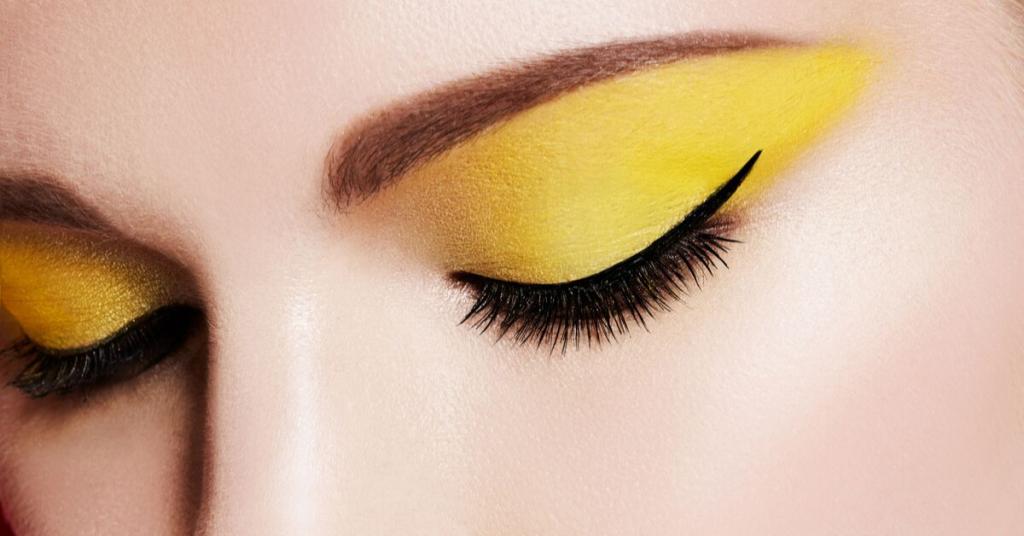 ojo de mujer cerrado maquillado con sombra amarilla y eyeliner negro