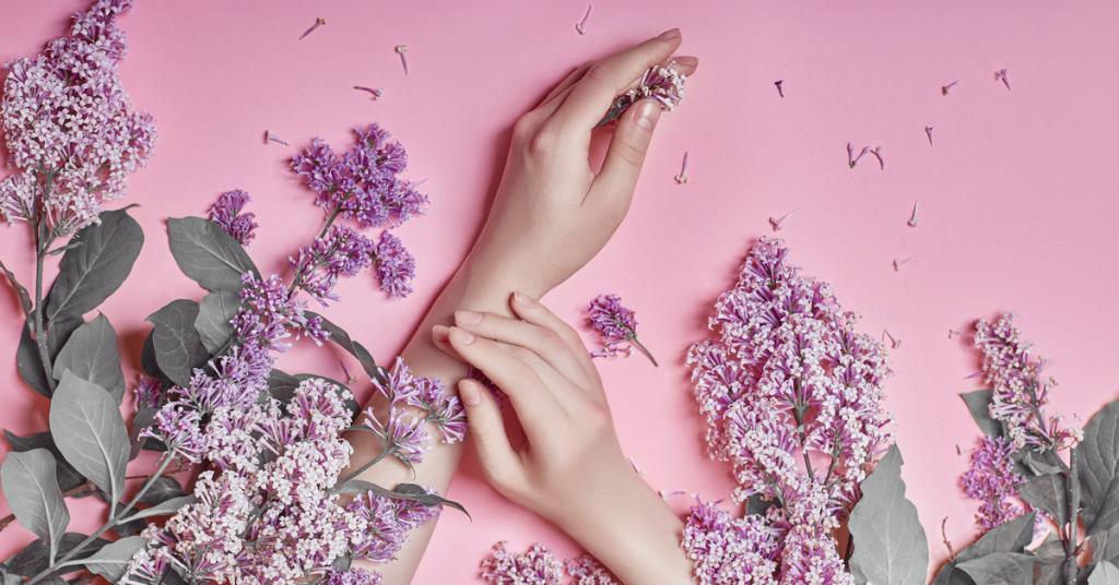 manos de mujer siobre un fondo rosa y alrededor flores de lavanta