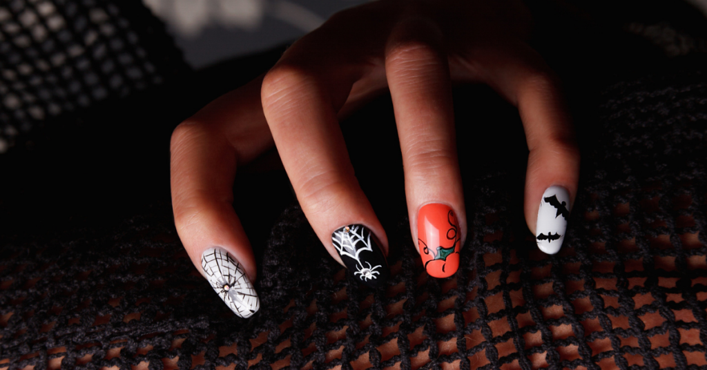uñas de mano de mujer pintadas con motivos de halloween como arañas murcielagos etc