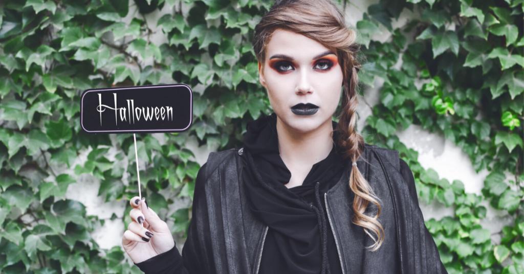 chica joven con los labios pintados de negro, los ojos con sombras y la cara blanca lleva una trenza al lado y sostiene vestida de negro un cartel que dice halloween