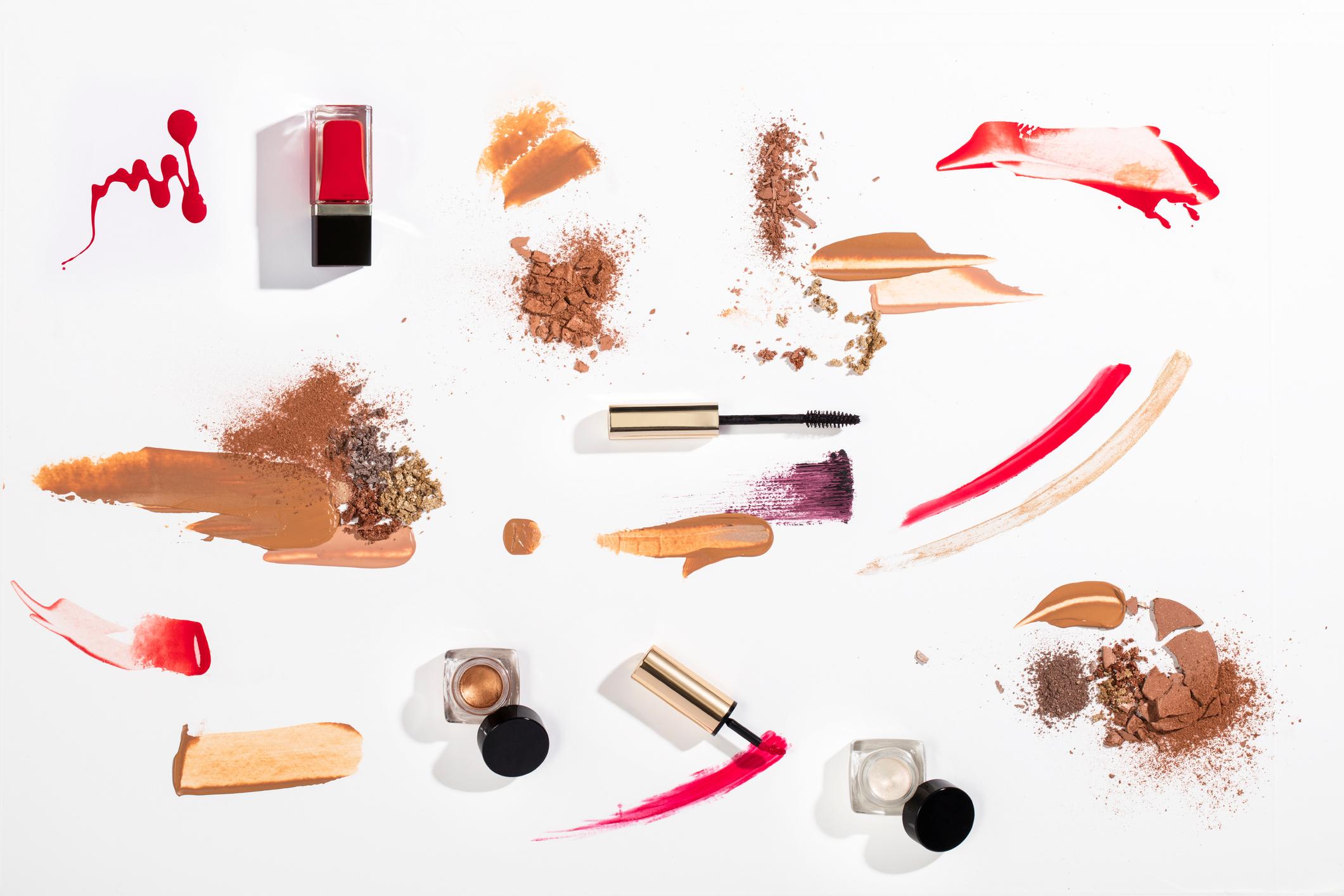 productos de belleza y su contenido líquido y en polvo esparcido sobre un fondo blanco