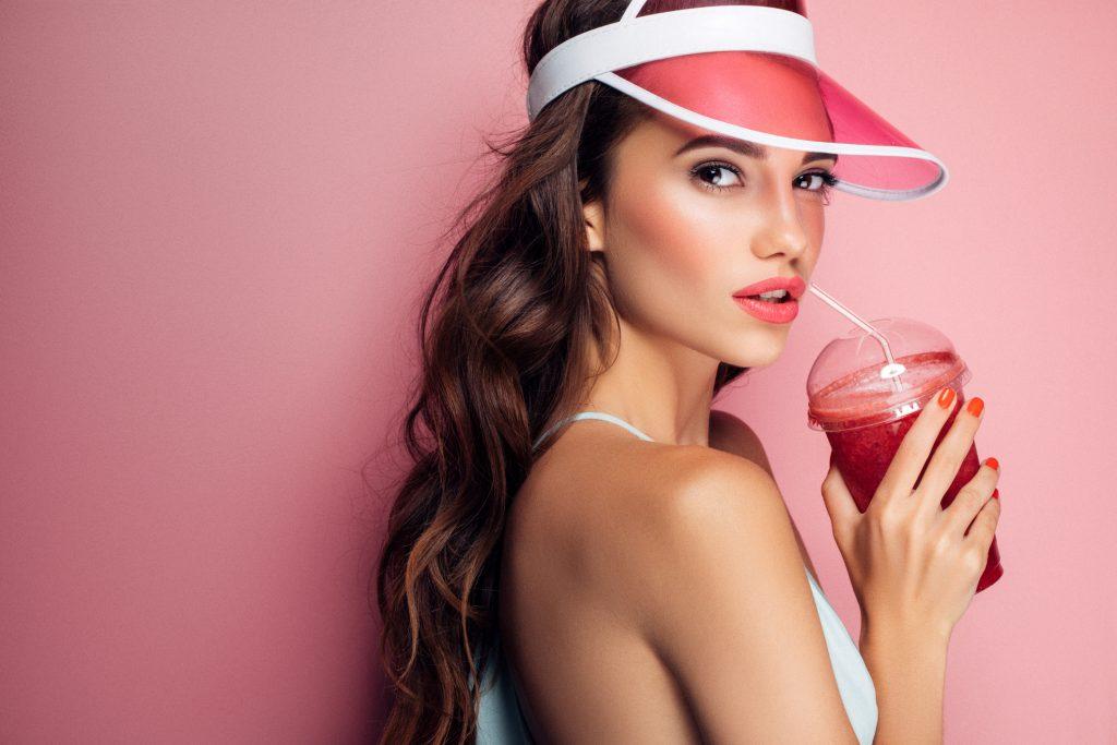 chica joven y guapa mira de perfil con una visera rosa y un smoothie de frutos rojos sobre un fondo rosa