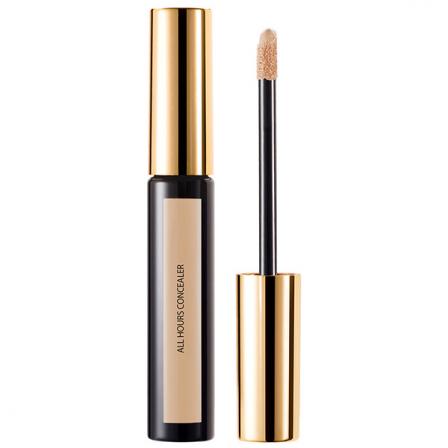 corrector maquillaje en un recipiente alargado junto a un pincel para aplicarlo con el mango dorado