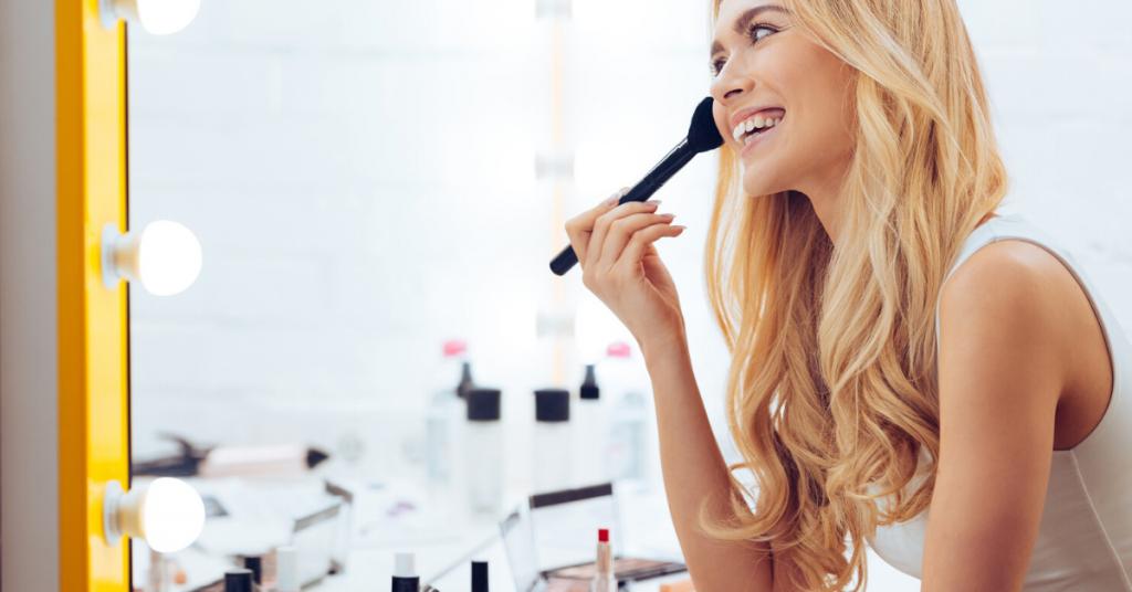Vista lateral de la alegre joven maquillarse y mirar su reflejo en el espejo mientras está sentado en el tocador