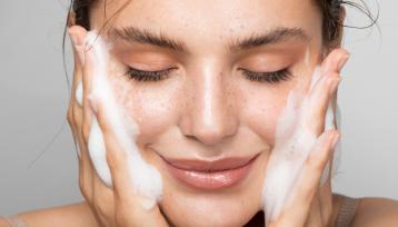 Primerísimo primer plano de una bella mujer con una piel perfecta mientras se limpia la cara