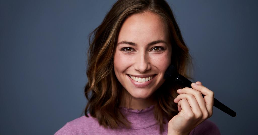 Impresionante morena sonriente aplicando maquillaje, retrato