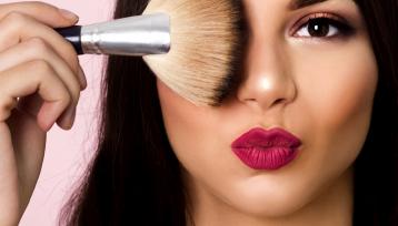 primer plano de una chica joven con los labios pintados de rojo en forma de beso y una brocha de maquillaje tapando un ojo