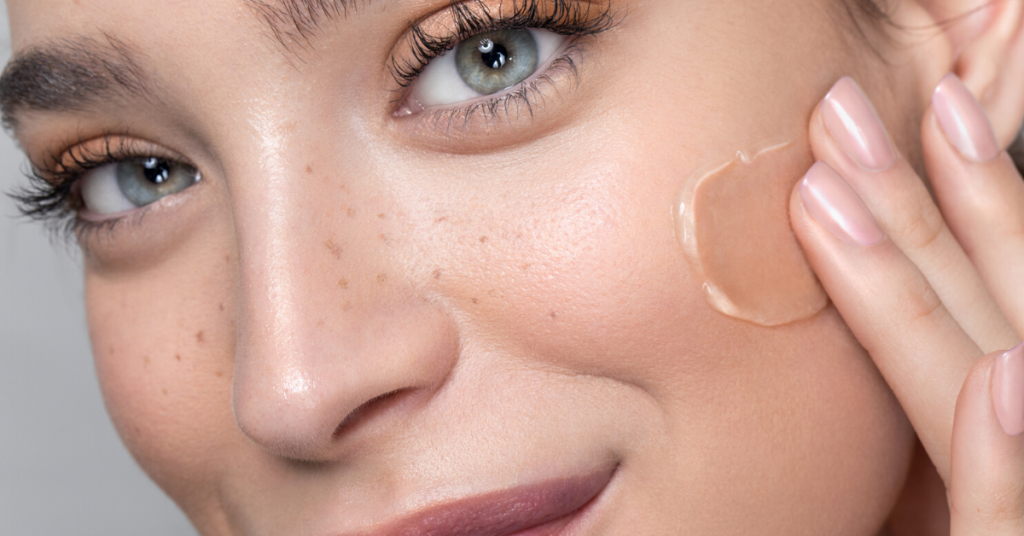 plano detalle del rostro de una chica joven con los ojos azules y pecas que se echa maquillaje en crema en la cara