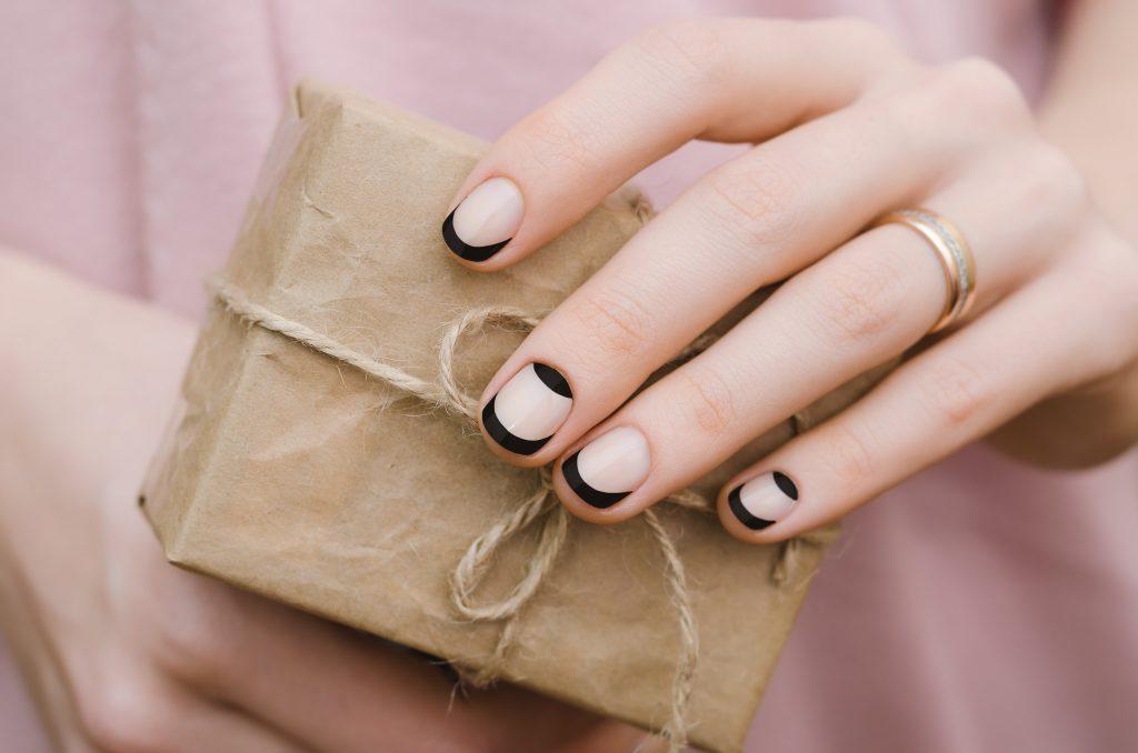manos de mujer con la manicura francesa en negro hecha sostiene un pequeño paquete envuelto en papel marrón