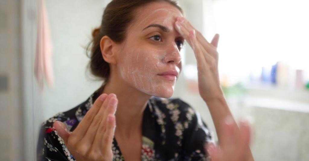 mujer joven se limpia la cara con las manos y una espuma blanca frente al espejo de un cuarto de baño
