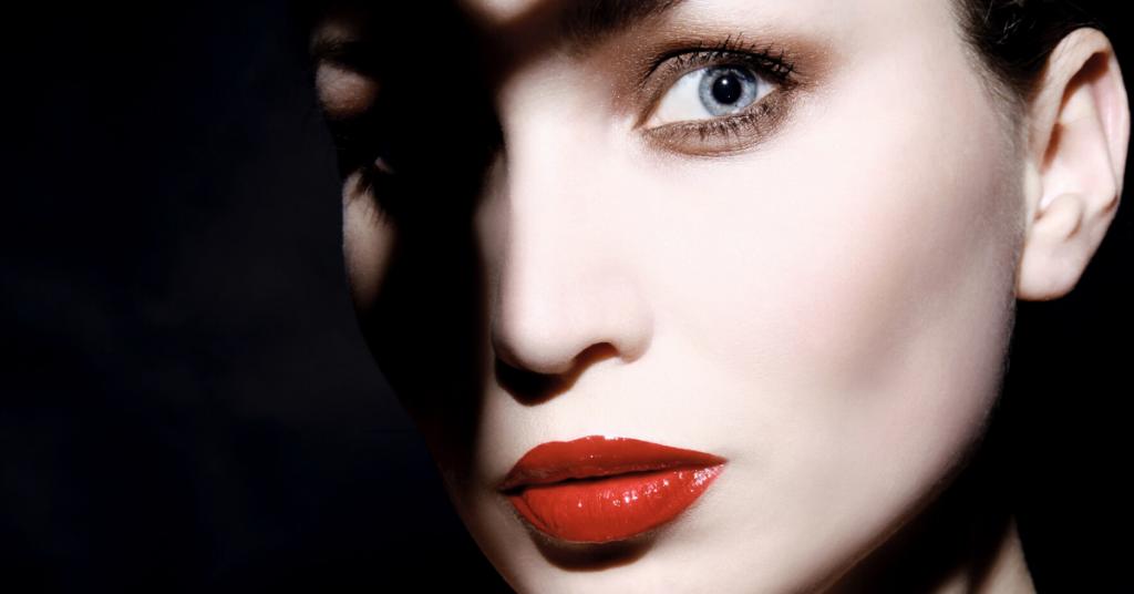 primerisimo primer plano de una mujer joven con los labios pintados de rojo cuyo rostro no vemos al completo porque lo oculta una sombra