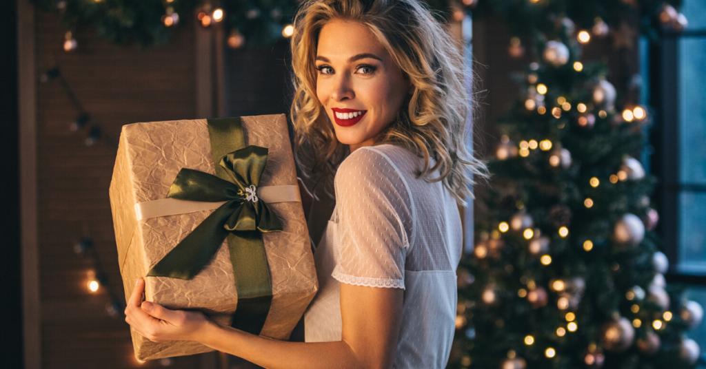 chica joven con un regalo en las manos en un entorno muy navideño