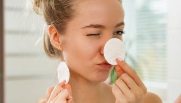 Joven hermosa mujer limpiar su piel de la cara con algodón