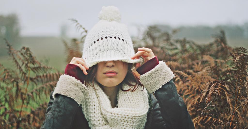 chica joven en un exterior invernal se tapa media cara con un sombrero blanco