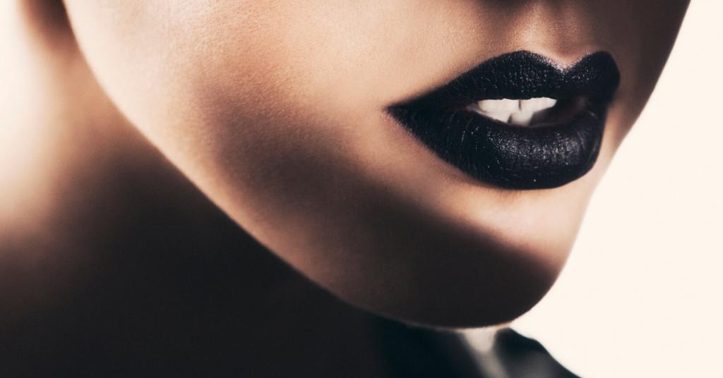 foto detalle de los labios de una mujer joven pintados con carmin negro oscuro. Una sombra cubre parte de la barbilla y el cuello.