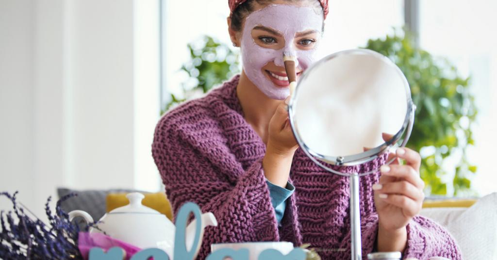 Mujer joven que aplica la máscara facial. Está sentada en su cama mirando al espejo y cuidando su piel durante la mañana del fin de semana