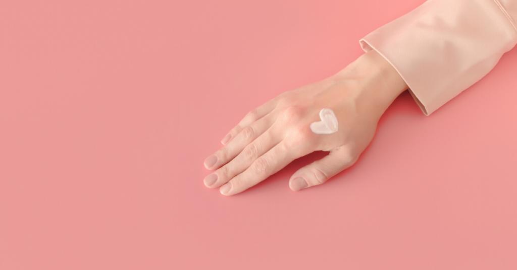 La mujer aplicó el frotis en forma de corazón de la loción poner crema a mano. Concepto positivo del cuerpo de amor propio. Blog femenino y plantilla de redes sociales. Minimalismo estilo fondo rosa milenario