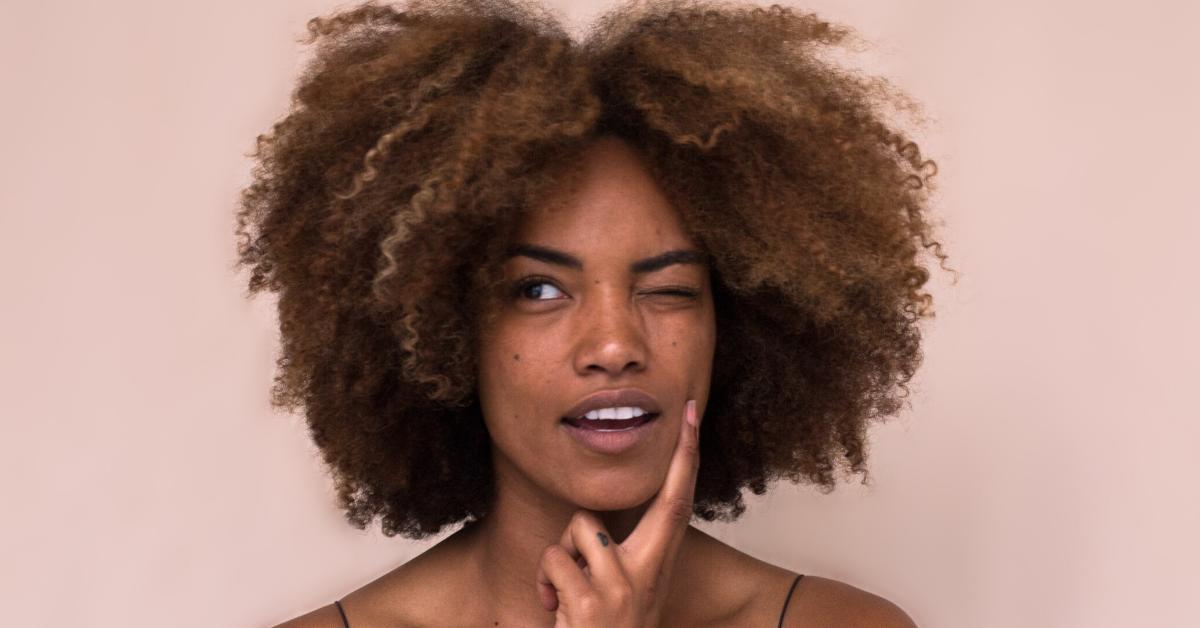 chica joven de color con el pelo rizado guiña un ojo y se lleva el dedo a la cara en gesto de duda